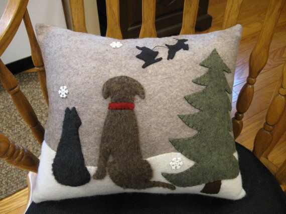 Children arent the only ones who anticipate Christmas! This pillow features a dog and cat looking up at the sky as Santa and his reindeer fly off into the night. It is a quiet Christmas eve and the snow is gently falling. Ive stitched the dog and cat out of furry plush material for a more realistic effect. Ive used wool felt in colors of mottled olive, cobblestone, brown, white and black. I wonder what these two friends are wishing for?  The pillow is my own design and is all hand stitched…