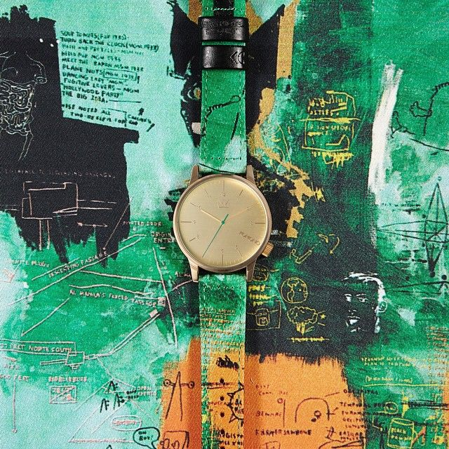 Jean-Michel Basquiat x Komono Winston Untitled, 1984. Deep, royal greens and golden hues on the printed fabric wristband reference the dark and mysterious princely figure central to Basquiat's work.