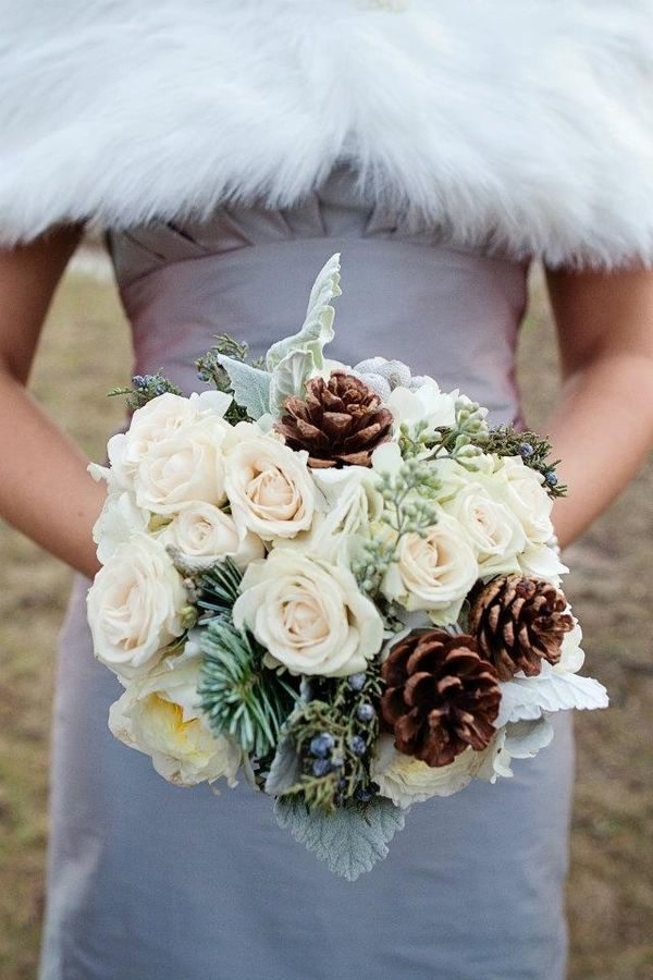 Woodsy wedding bouquet with white roses, pine cones, evergreen and juniper berries.