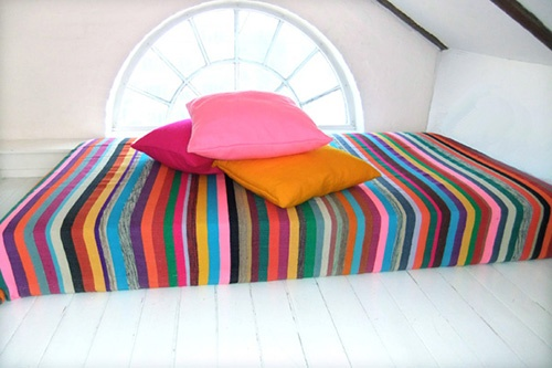 Happy multicolored stripes on the bed. Handwoven bedcover by kira-cph.com