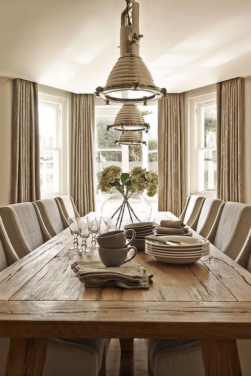 Taupe dining room features a long reclaimed wood dining table lined with taupe curved arm dining chairs illuminated by Ralph Lauren Home Montauk Pendants placed in front of bay windows dressed in taupe curtains hung high.