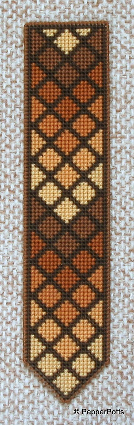 Worked on 14ct plastic canvas in a cross stitch, using various shades of brown stranded cotton leftovers. The diamonds were worked first, then the contrasting lines filled in in a very dark brown stranded cotton. It is backed with thin craft foam using a double sided adhesive film.