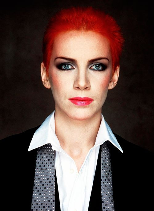 [Annie Lennox with fluffy red-orange hair and flawless makeup, wearing a suit]