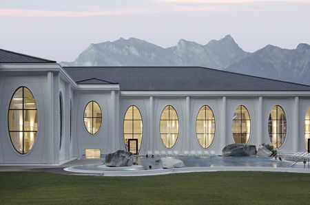 Smolenicky & Partner Architektur of Zurich have completed thermal baths featuring oval apertures between tall wooden columns at Bad Ragaz, Switzerland. Above photo is by Walter Mair Called Tamina Thermal Baths, the project incorporates an indoor pool, sauna, shops and restaurant. Above photo is by Walter Mair The 20 metre-high structure includes 115 columns. Above