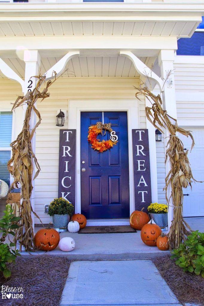 Тыквы, фонари Джека, кукурузные стебли, вазоны с цветами и венок из осенней листвы украшают вход в этот дом. .