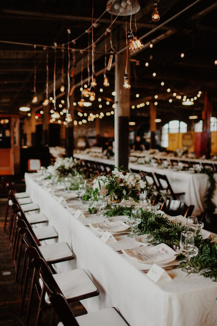 Head Table With Fern Runner And A Suspended Edison Bulb Installation At The Piquette Plant In Detroit Santa Barbara Destination Wedding Planner