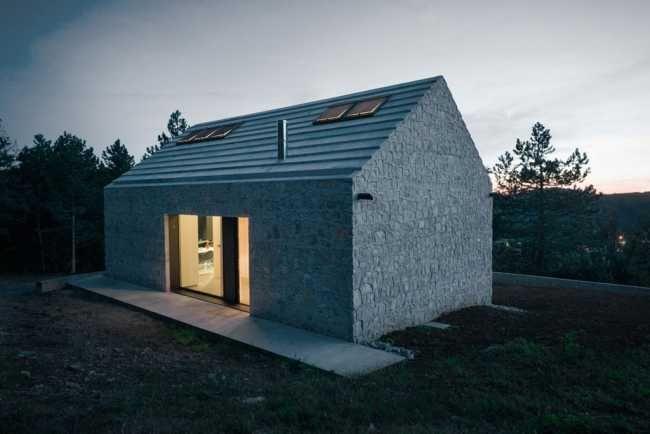 Jednoliaty exteriér je prerušený výraznými presklenými prvkami z troch strán domu a tiež strešnými oknami. Dom teda nemá núdzu o denné svetlo.