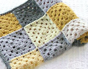 A cozy crochet baby blanket in blue gingham is perfect for your baby boy! This white, blue and gray granny square blanket is crocheted in a patchwork