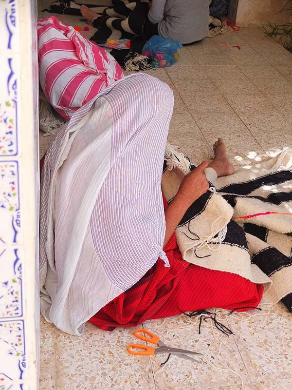 The Bedouine woman is finishing the colorful stiching of a kira-cph rug