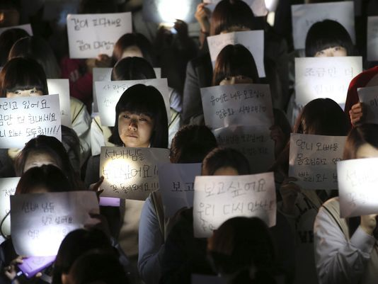 Students hold papers and candles and pray for safe return of their friends aboard the sunken ferry Sewol at Danwon High School in Ansan, south of Seoul, on April 18, 2014. (Photo: AP)