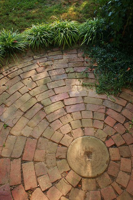 Circular brick patio- the casual and informal design is appealing.