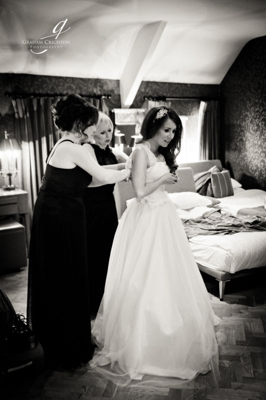 Black and white image of brides maids helping bride into her wedding dress in hotel room www.grahamcrichton.com