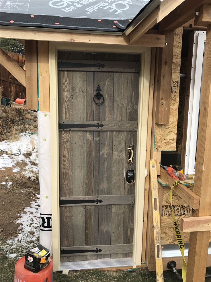 Rustic door made from old wood attached to cheap steel door for outdoor bar at cabin.