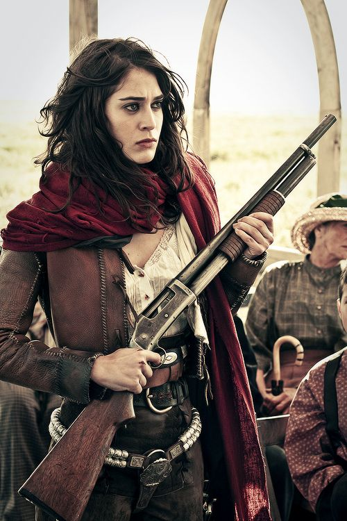 [ Image: A film still of a pale skinned woman with brown eyes and long dark hair. She wear a red scarf over a mostly leather ensemble in the style of the Wild West, and is holding a pump-action shotgun. ]    Lizzy Caplan as Juliette Flowers