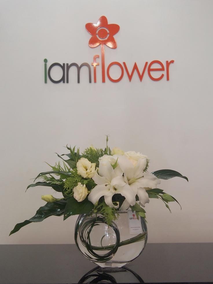 Vase arrangement with white lilly,white eustoma,white rose and greenery.