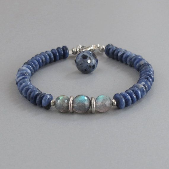 Denim blue polished Lapis Lazuli surround a trio of Labradorite rounds and handmade silver beads and close securely with a lobster claw clasp.