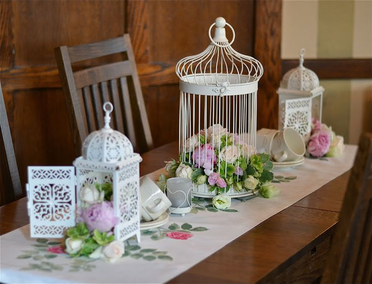 Cream bird cage and lanterns filled with cream, pink and green flowers. Peonies, hydrangeas, roses and lisianthus tumble out of the containers onto the tablecloth.