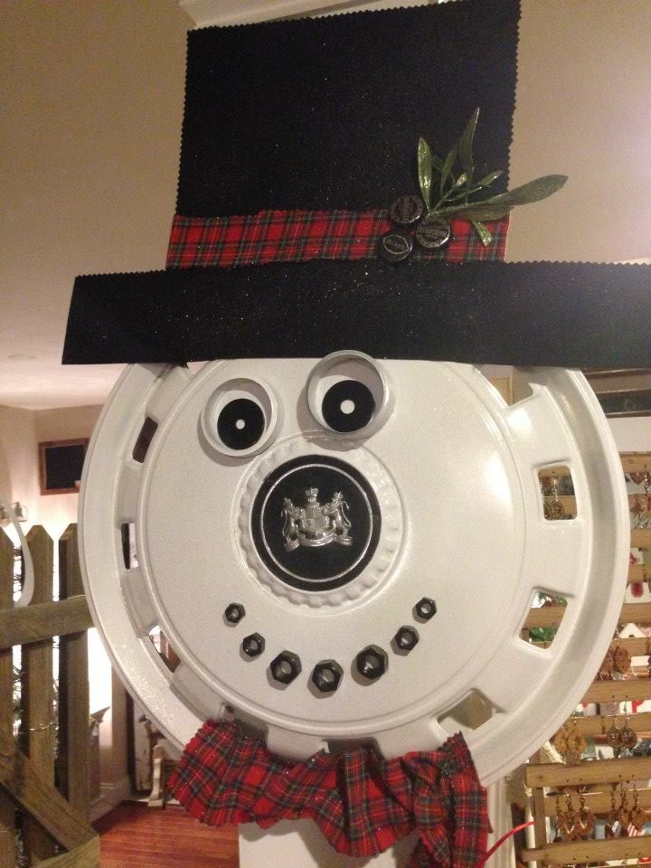 Up-cylced snowman made from hub cap, nuts, pipe ends, beer caps and flannel shirt for his scarf and hat band. Adorable!