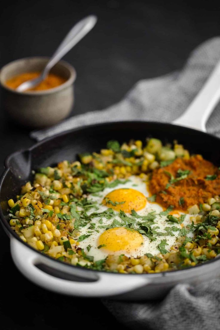 A perfect summer egg skillet featuring a simple zucchini and sweet corn cilantro hash plus grains and legumes if desired.