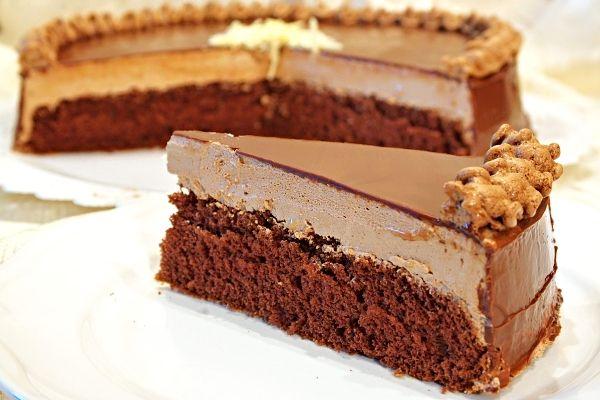 Dort z tmavého piškotového korpusu potřený kakaovým krémem, ozdobený čokoládovou polevou, dozdobený zbytkem krému z náplně.
