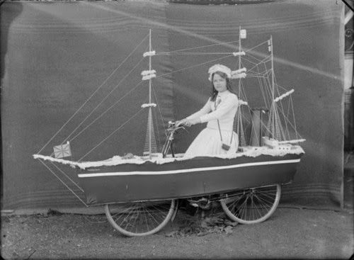 British Paintings: Young woman on a bicycle float of Robert Falcon Scott's boat the 'Terra Nova' by Adam Henry Pearson Maclay, ca. 1910-1913...