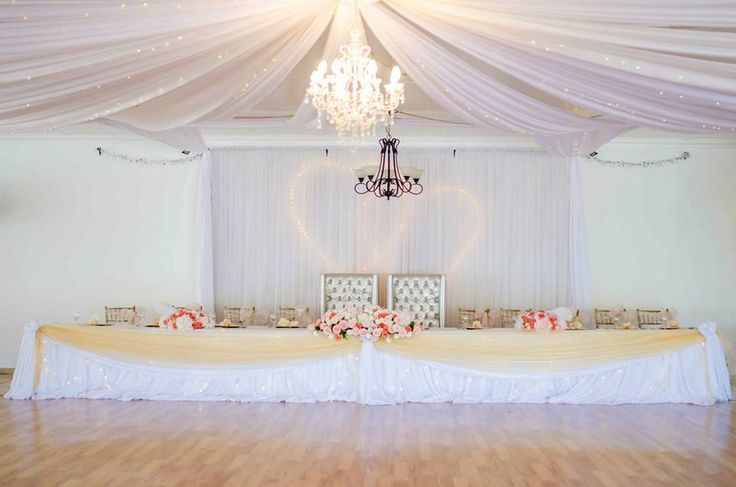 Monte Vista Venue main table setup for a gold and peach wedding. Gold draping with a white skirt, peach and white flowers in rose bowls and rose boats with fairy light hearts behind the table