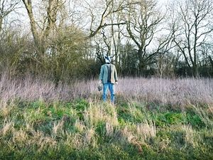 Charles Foster near woods wearing a badger mask