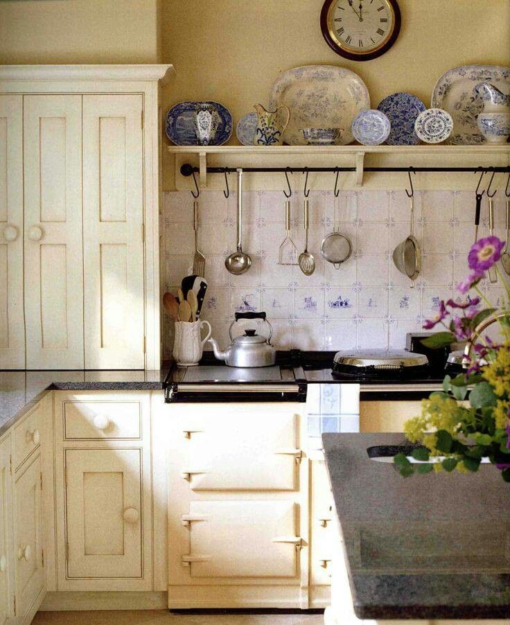 possibly from The English Home    I love the butter-yellow walls, antique white cabinetry, and blue dishes...the tool rack is also a great idea!