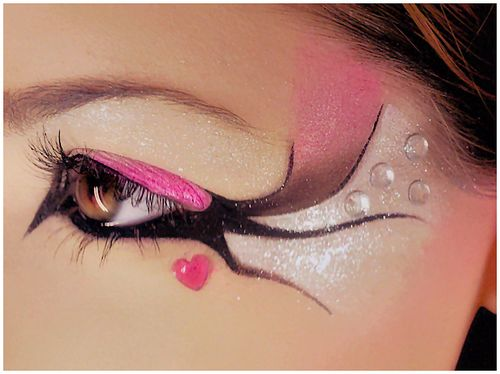 Artistic pink, silver and black fantasy eye make-up accented with gems.