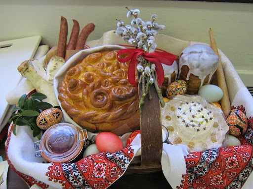 This basket lined with a traditional Ukrainian embroidered cloth is filled with symbolic foods of Easter ready to be blessed, including kielbasa, horseradish root, beet and horseradish condiment, flavored butter, babka, Pysanky eggs, and the paska.