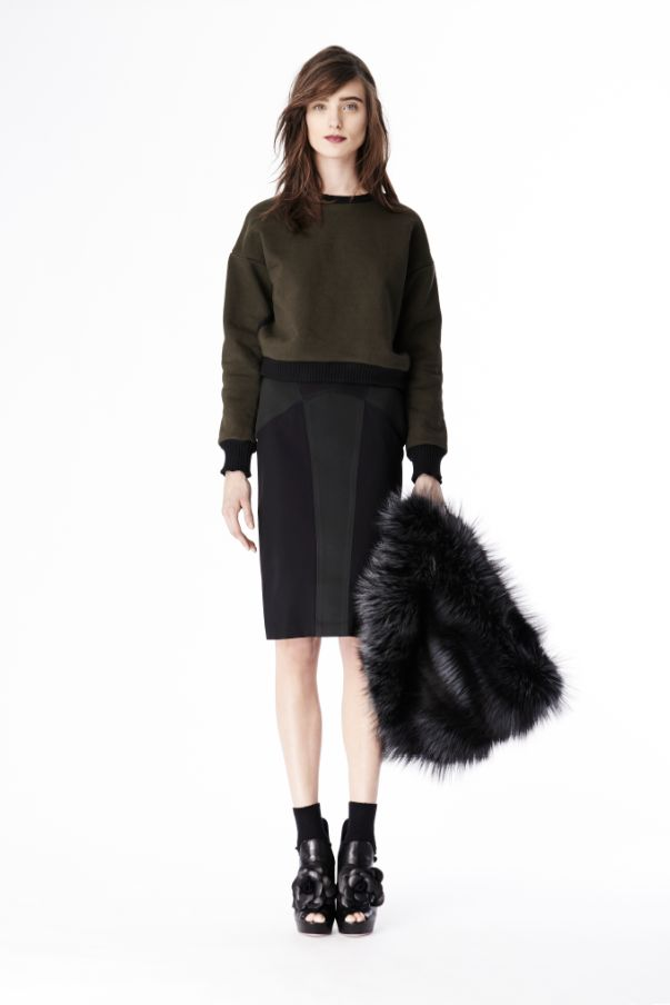 Look 29. Cropped olive green sweatshirt over a tight knee length paneled black and gray skirt.