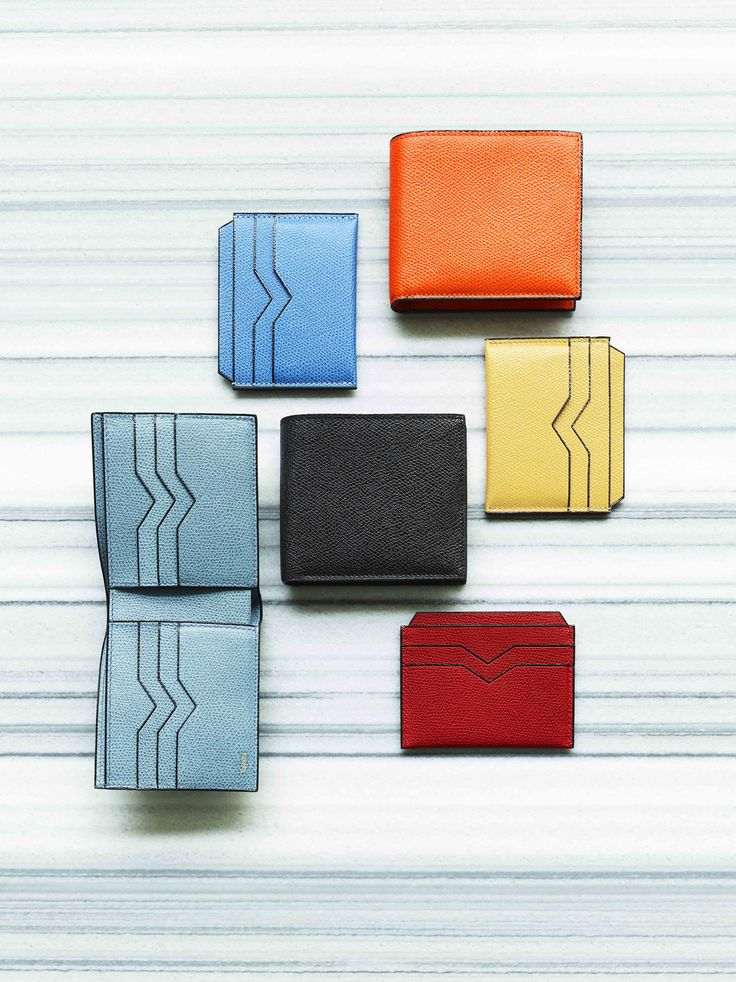 Valextra: Leather card case in blue, yellow and red. $240 each. Leather bi-fold wallet in blue, orange and black. $450 each. #holtsmag