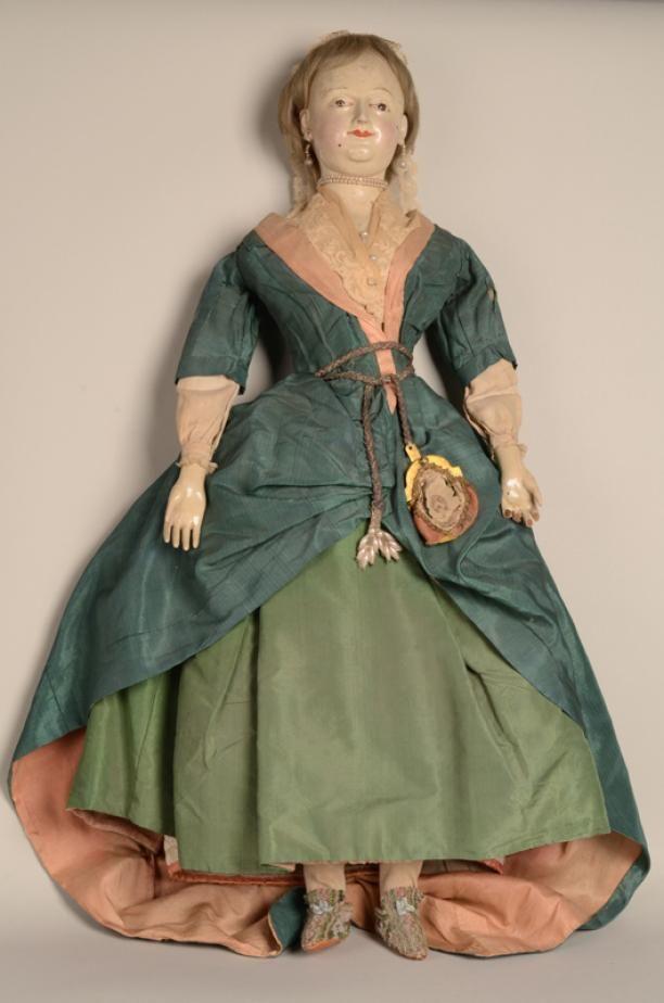 Pop | Modemuze - De pop is gekleed naar de mode van 1760, groene rok met donkergroene overjapon, afgezet met zalmkleurige zijde. Aan de hals kanten fichu, om de taille een zilveren koord waar een beugeltas aan hangt. Linnen ondermouwen. Op het blonde haar een kapje met kanten barbes, dubbele parelsnoer om de hals en aan de oren parelen oorbellen. Als onderkleding draagt zij een witte zijden onderrok van Zaans stikwerk, een corset, een wit linnen onderrok, een wit keper broek, wit katoenen…