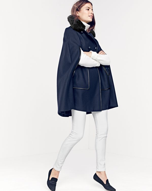 J.Crew women's Collection faux-fur-collar cape with leather piping, cambridge cable turtleneck sweater, lookout high-rise Cone Denim® jean in white and Georgie suede penny loafers. To pre-order, call 800 261 7422 or email verypersonalstylist@jcrew.com.