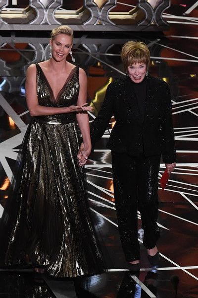 Charlize Theron Photos Photos - South African-US actress Charlize Theron (L) and US actress Shirley MacLaine arrive on stage to present the Best Foreign Language Film award at the 89th Oscars on February 26, 2017 in Hollywood, California. / AFP / Mark RALSTON - 89th Annual Academy Awards - Show