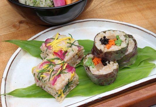 押し寿司はおかひじきや紫玉ねぎ、かぼちゃの一種のコリンキー。 千切りにして酢飯ご飯に混ぜあわせて 型に入れて作ります。 巻きものはサニーレタスと生春巻きで巻いたもの。 中には人参と長ひじき、いんげん、おからこんにゃくのベジハム風。 みょうがの新芽の葉の上に盛りつけ。