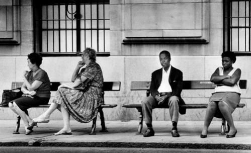 Whites sit on a bus stop bench with blacks two weeks after the city of Johannesburg in South Africa allowed blacks to travel on 'whites-only' buses in February, 1990.