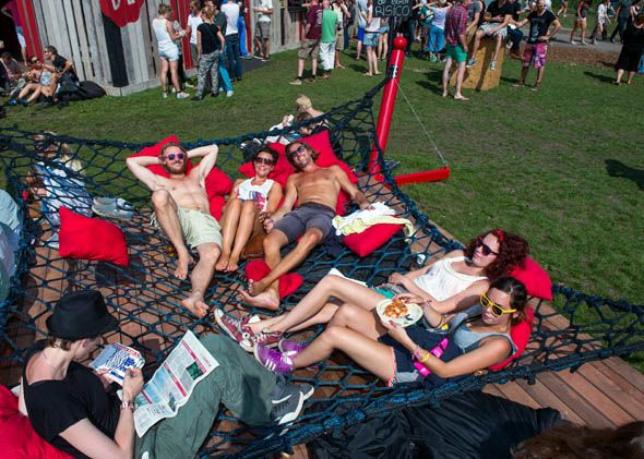 Visitors to the Lowlands Festival relax on a giant hammock on the second day of the Lowlands festival in Biddinghuizen, the Netherlands, on ...