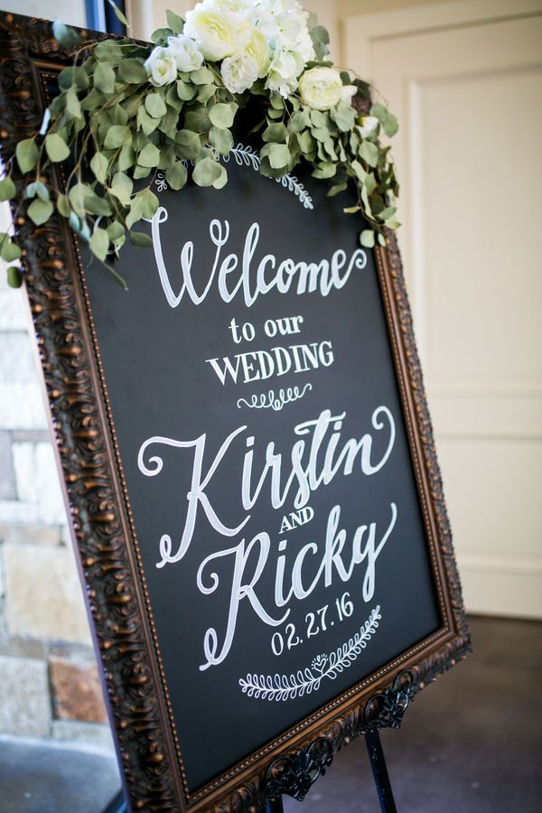 A chalkboard wedding ceremony welcome sign with calligraphy font and greenery garland.