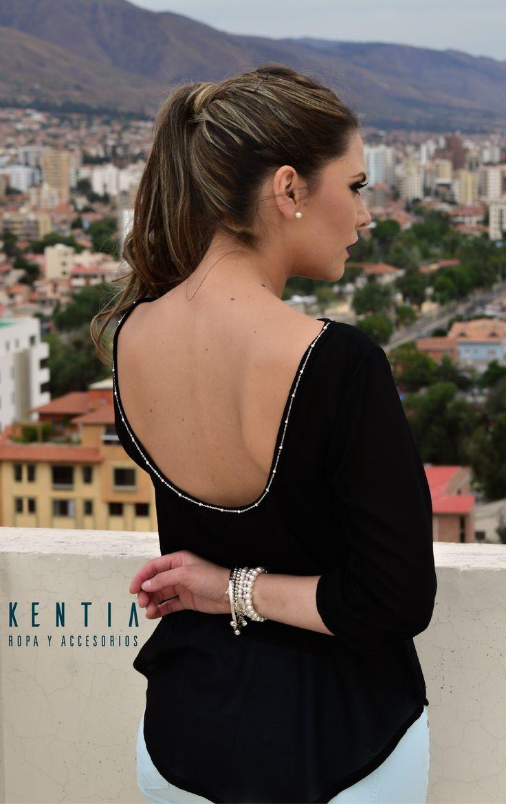 Blusa de gasa con escote en la espalda y manga 3/4. Lleva cadena metálica en la espalda.