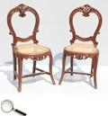 A pair of Victorian mahogany chairs, of Goan origin, with balloon backs with carved decoration over rattan seats, on cabriole legs.     18 in L x 17 in B x 36 in H
