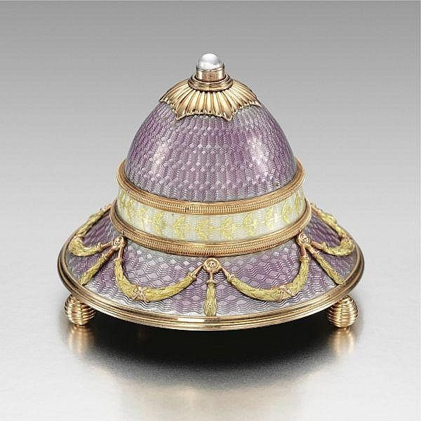 A Fabergé two-colour gold and guilloché enamel bell push, workmaster: Michael Perchin, St. Petersburg, 1899-1903 the domed body decorated in lilac and oyster translucent enamel over engine-turned grounds, the oyster band further embellished with a gilt foliate border, surmounted with a gadrooned hexagonal mount set with a moonstone pushpiece, on a circular spreading base mounted with finely chased ribbon-tied laurel swags, marked Fabergé with workmaster's initials and scratched inventory…