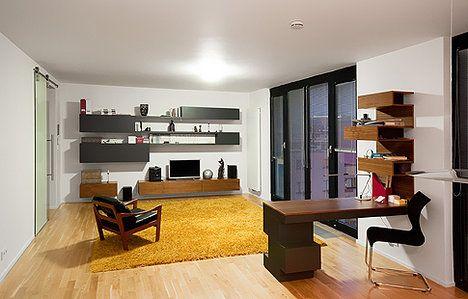 Obývací prostor s knihovnou, televizí, sezením a pracovním stolem, který ho odděluje od kuchyňské části. V době naší návštěvy zde ještě chyběla sedací souprava, již majitelé dopraví v příštích týdnech. Šedobílou barevnou kombinaci rozjasnil žlutý koberec, který ladí i s dřevěnou podlahou; SKUTEK architecture.