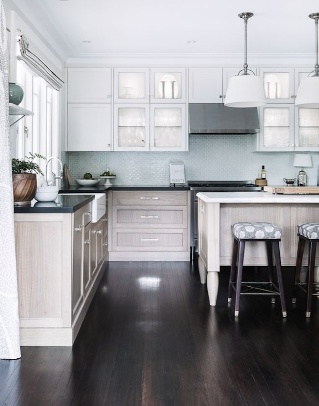 Modern farmhouse kitchen design featuring white upper cabinets, pale wood lower cabinets and island, black granite countertops and white granite countertops on the island, contemporary pendant lights and dark hardwood floors - Home Decor & Decorating Ideas - jacquelynclark.com