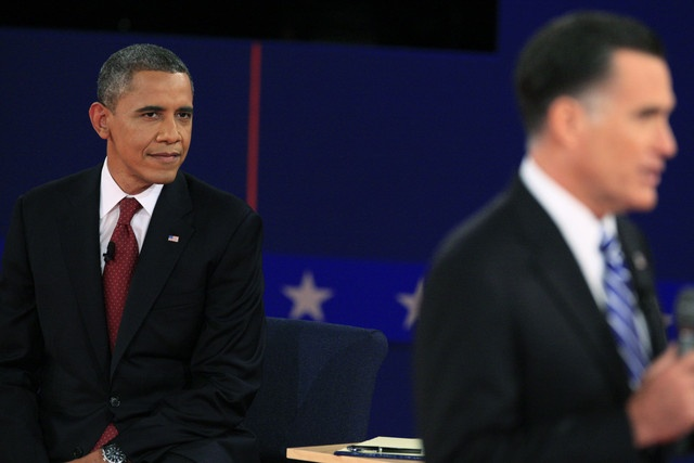 85 10/17/12 U.S. President Barack Obama, left, looks on as Mitt Romney, Republican presidential candidate, speaks during the second presidential debate at Hofstra University in Hempstead, New York, on Tuesday, Oct. 16, 2012.