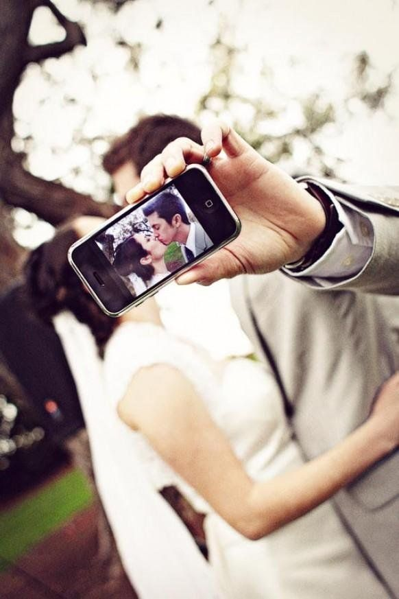 In this technological age, this is a clever shot to take a picture of a kiss.