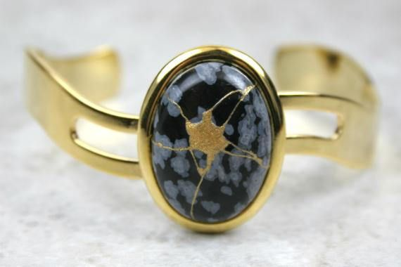 Kintsugi (kintsukuroi) cuff bracelet with a snowflake obsidian stone cabochon with gold repair in a gold plated setting by A Kintsugi Life