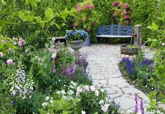 Steinweg in einem Garten, der zu einer Bank führt.