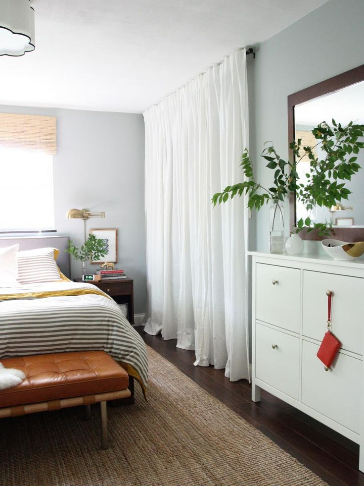 A simple white curtain hung high and wide adds to the pared-down, natural look of this sweet bedroom designed by House Tweaking. A curtain is a great way to hide a cluttered closet or even add an extra bit of space.