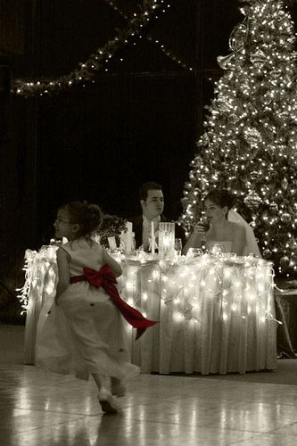 Lights Around The Bride And Grooms Table With Christmas Tree In Background.  Love The Flower Girl In The Foreground With The Red Sash Colored.